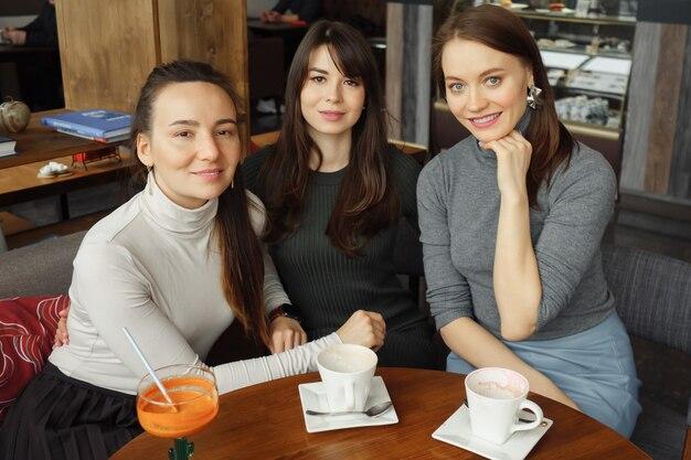 Trois femmes copines avec des boissons dans un café parlent et regardent la caméra