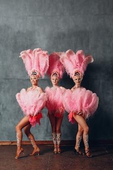 Trois femmes en costume de cabaret au plumage de plumes roses.