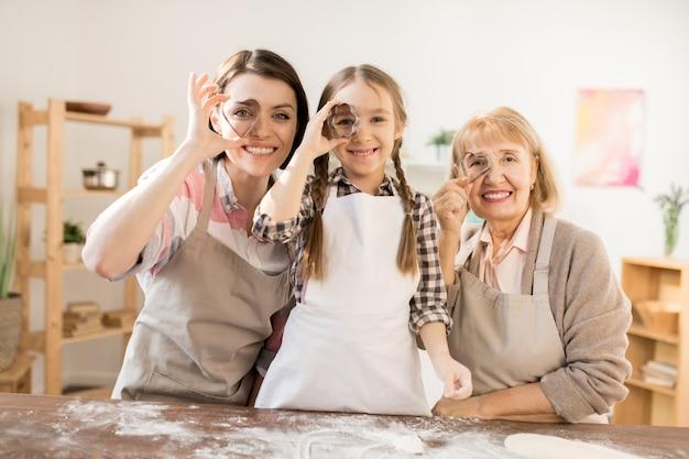 Trois femmes gaies en tabliers tenant des emporte-pièces par leurs yeux en se tenant debout près de la table de cuisine