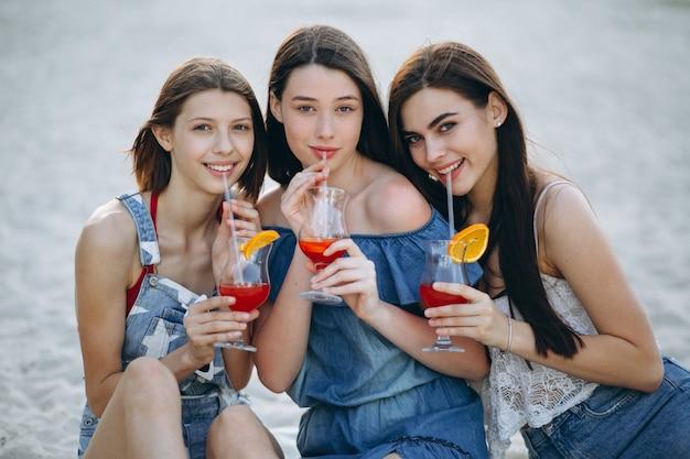 Trois femmes heureux à la plage avec des cocktails
