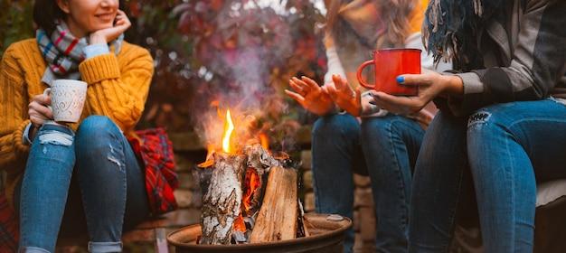 Trois femmes meilleures amies assises autour d'un feu de joie dans des vêtements décontractés s'échauffant et communiquant