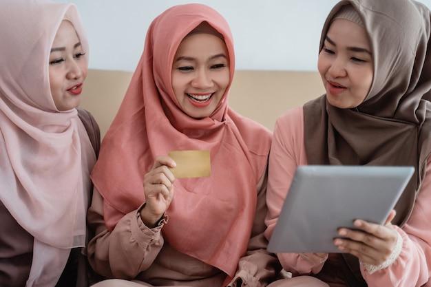 Trois femmes musulmanes utilisant une tablette pour acheter les articles dans la boutique en ligne lorsqu'ils restent à la maison