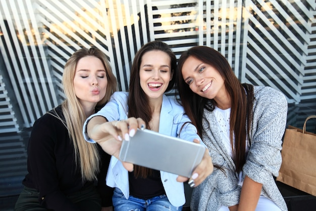 Trois femmes prenant un selfie lors de leurs achats dans un magasin de vêtements. ils sont heureux et sourient à la caméra. concept d'achat, également lié à la dépendance aux médias sociaux