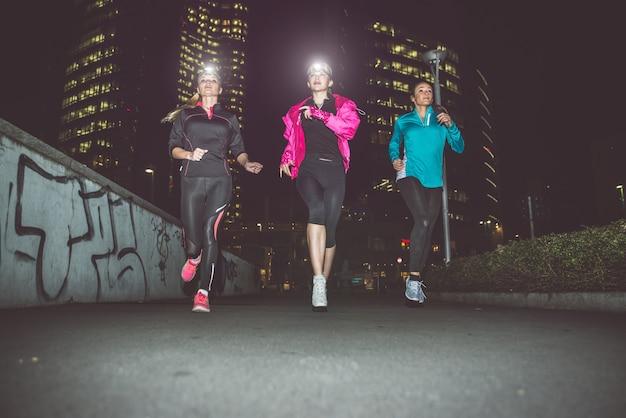 Trois femmes qui courent dans la nuit dans le centre-ville
