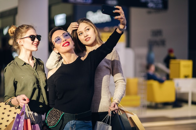 Trois femmes avec des sacs à provisions prenant selfie avec leur smartphone