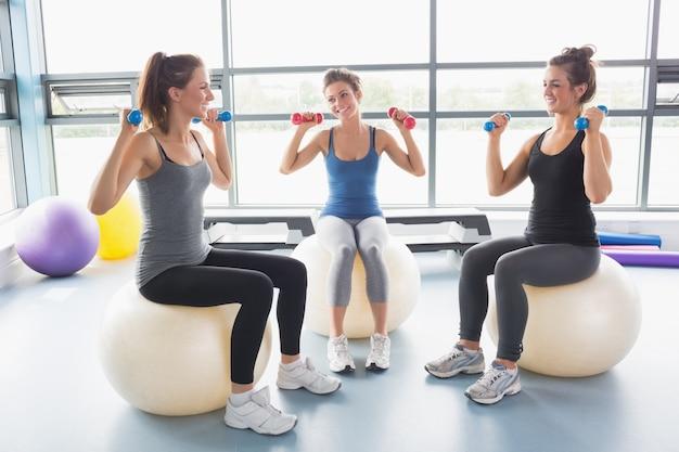 Trois femmes soulevant des poids sur des balles d'exercice