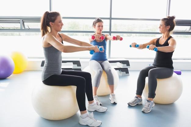 Trois femmes soulevant des poids ensemble sur des balles d'exercice