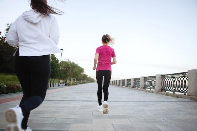 Trois femmes en tenue de sport courent le long de l'allée du parc de la ville en été. vue d'en bas. vue arrière.