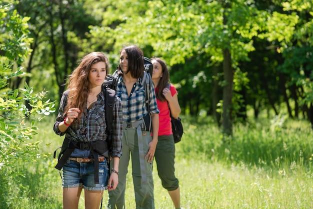 Trois femmes touristes en forêt avec des sacs à dos