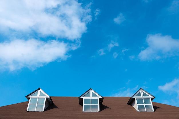 Trois fenêtres sur un toit de maison avec un beau ciel et fond de nuages