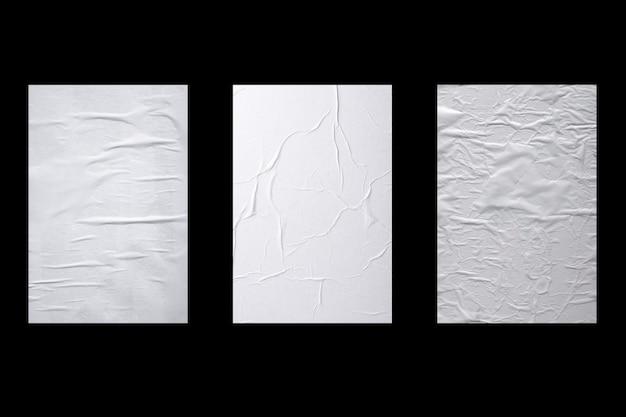 Trois feuilles de papier blanc froissé isolées sur fond noir.