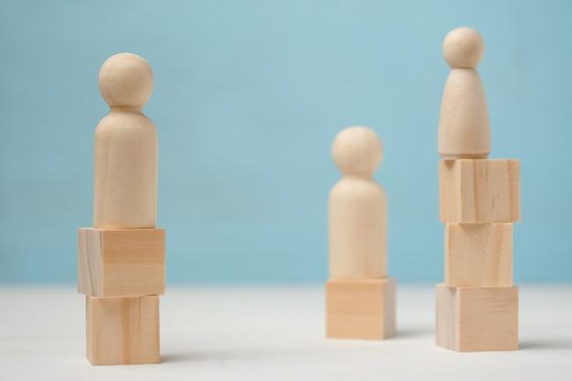 Trois figures abstraites en bois de personnes se tiennent à différents niveaux.