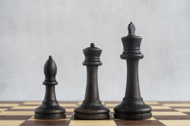Trois figures d'échecs noires sur l'échiquier
