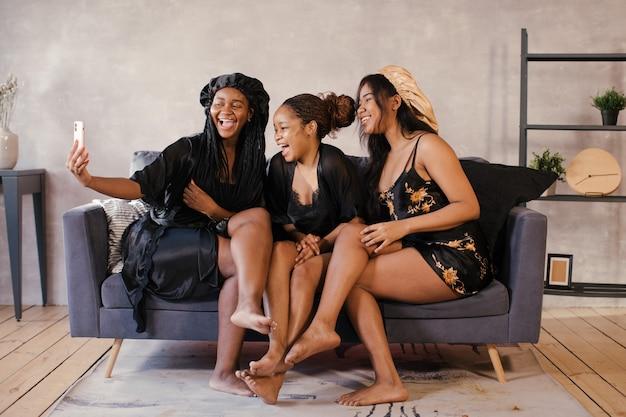 Trois filles afro-américaines positives du corps assis sur le canapé sont photographiées au téléphone