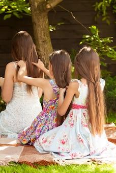Trois filles assises sur l'herbe au jardin et faisant des coiffures