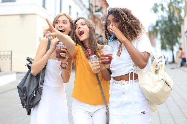 Trois filles branchées et branchées, des amis boivent un cocktail sur fond de ville urbaine.