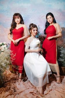 Trois filles debout et assis avec des fleurs