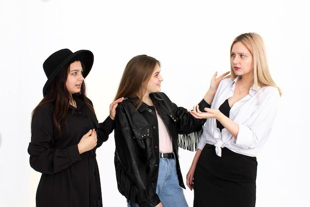 Trois filles discutent de quelque chose entre elles. photo sur fond blanc