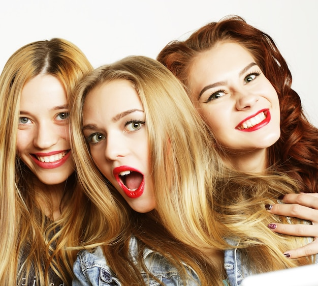 Trois filles élégantes meilleures amies se tenant ensemble et s'amusant