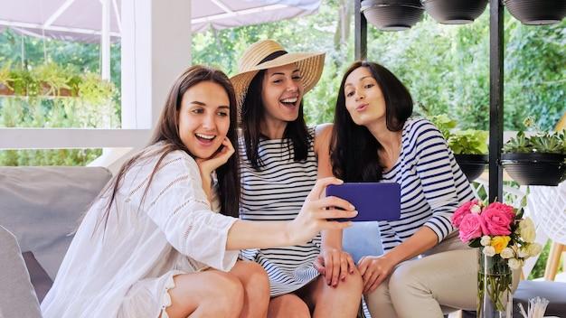 Trois filles gaies discutent et s'amusent en s'asseyant au café.