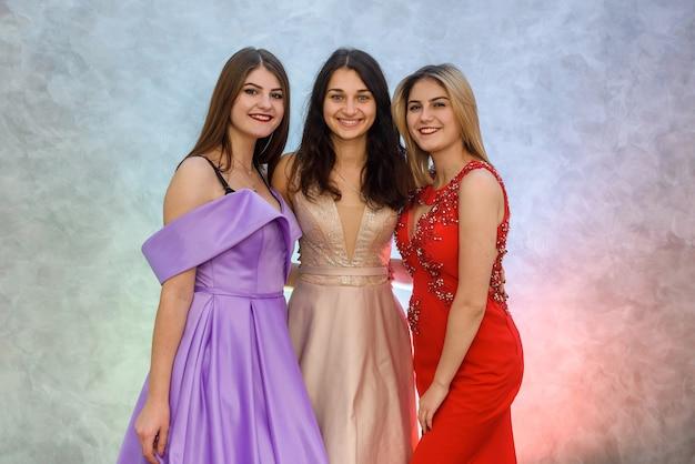 Trois filles heureuses en robes élégantes posant sur fond abstrait. concept de célébration