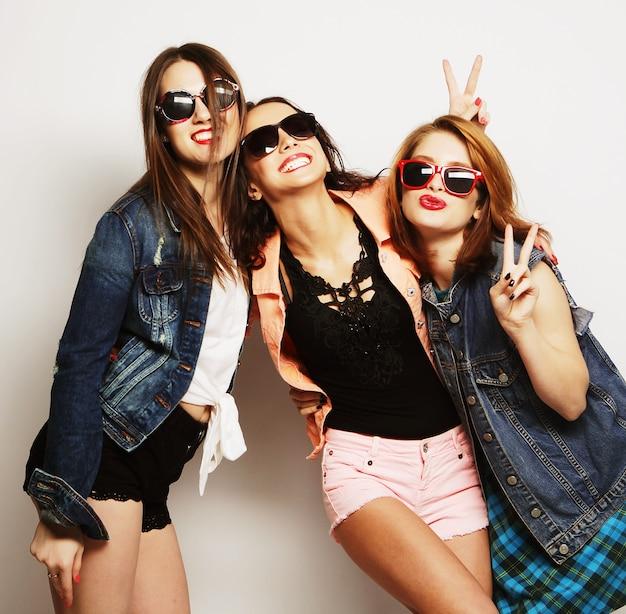 Trois filles hipster sexy et élégantes se tenant ensemble et s'amusant