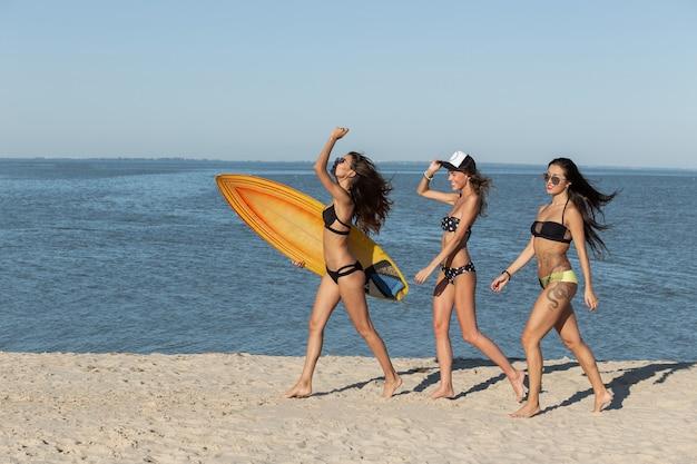 Trois filles minces et chaudes en maillot de bain marchent le long de la plage de sable près de la mer. l'un d'eux tient une planche de surf jaune. .
