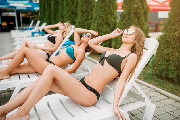 Trois filles minces se détendre sur des chaises longues à l'extérieur