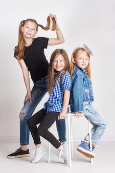 Trois filles posant, une école modèle pour les enfants.