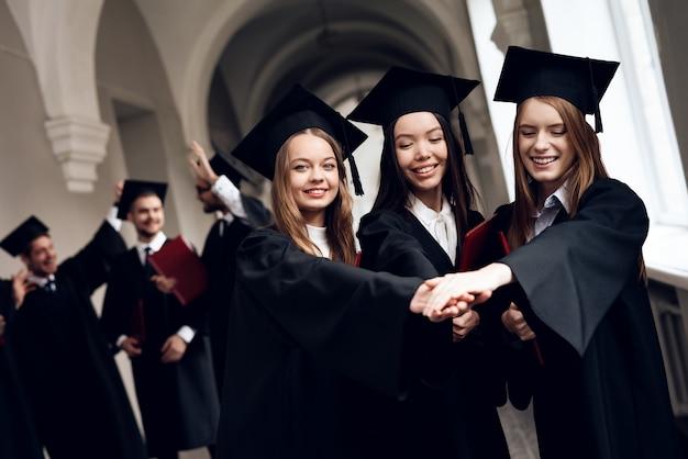 Trois filles posent pour une caméra à l'université.