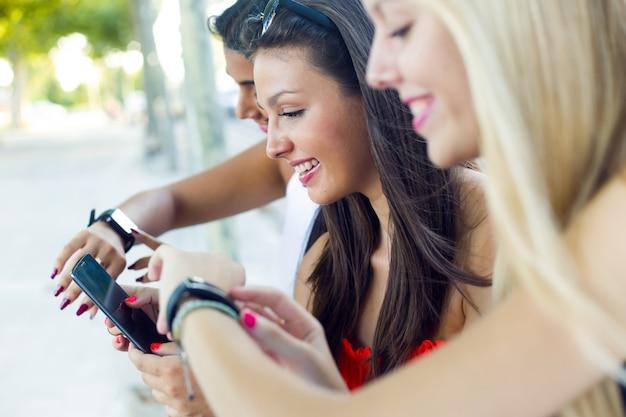 Trois filles qui parlaient avec leurs smartphones dans le parc.