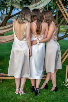 Trois filles en robes beiges se tiennent le dos sur fond de nature.