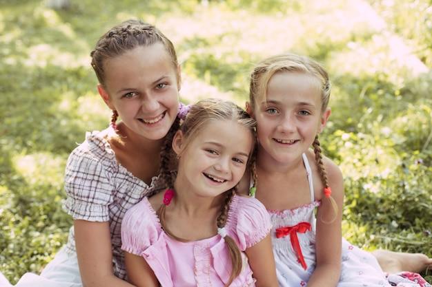 Trois filles s'assoient sur l'herbe et sourient