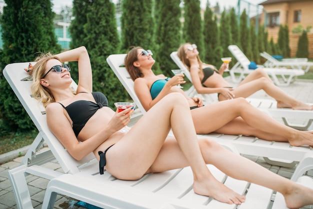 Trois filles se détendre et bronzer sur des chaises longues