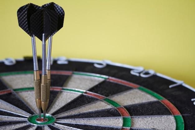 Trois fléchettes sur cible bulls eye de jeu de fléchettes, concept de victoire et réalisation des objectifs, mise au point sélective