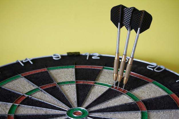 Trois fléchettes sur cible à triple anneau de jeu de fléchettes, concept de victoire et réalisation de l'objectif