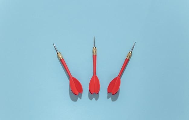 Trois fléchettes en plastique rouge avec pointe en métal sur fond bleu clair avec ombre profonde.