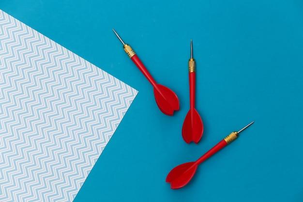 Trois fléchettes en plastique rouge avec pointe en métal sur fond bleu.