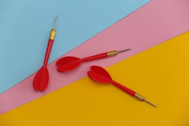 Trois fléchettes en plastique rouge avec pointe en métal sur fond coloré.