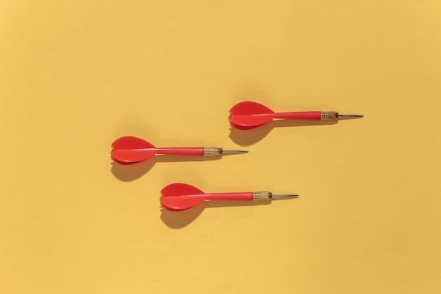 Trois fléchettes en plastique rouge avec pointe en métal sur fond jaune clair avec ombre profonde.