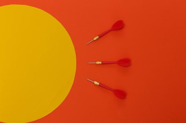 Trois fléchettes en plastique rouge avec pointe en métal sur fond orange avec cercle orange.. espace de copie