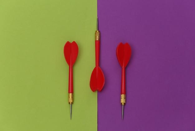 Trois fléchettes en plastique rouge avec pointe en métal sur fond vert violet.