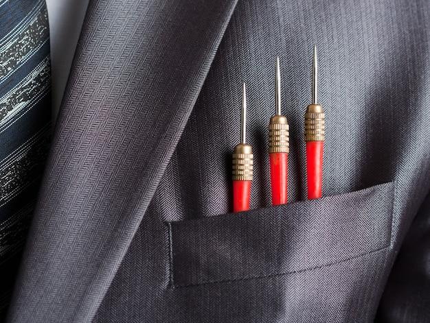 Trois fléchettes rouges dans la poche de costume homme d'affaires