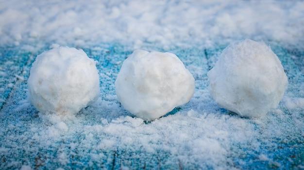 Trois flocons de neige sur une surface en bois bleue couverte de neige