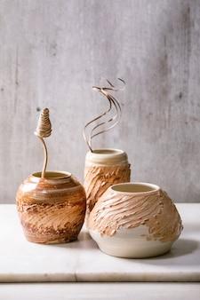 Trois formes différentes vases en céramique marron beige avec des fleurs sèches et des brindilles sur une table en marbre blanc avec un mur gris derrière. copiez l'espace.