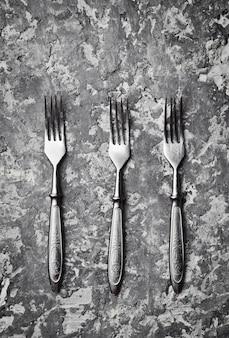 Trois fourchettes antiques sur une table en béton gris. vue de dessus.