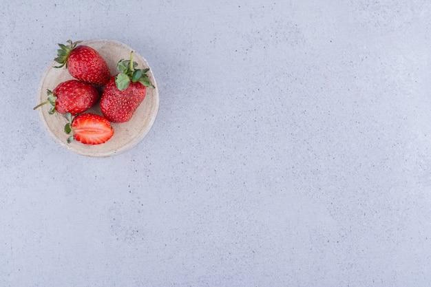 Trois fraises et demie sur un morceau de bois sur fond de marbre. photo de haute qualité