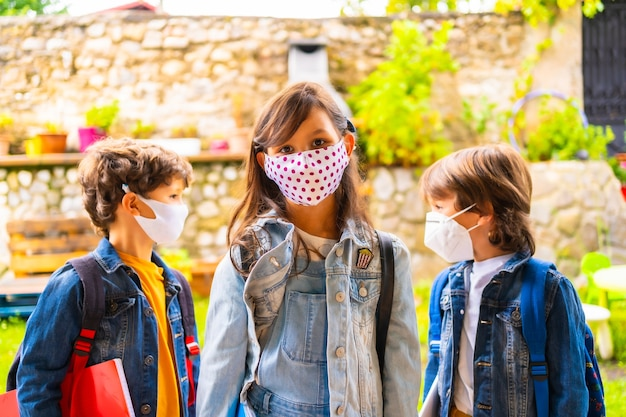 Trois frères enfants avec des masques faciaux prêts à retourner à l'école. nouvelle normalité, distance sociale, pandémie de coronavirus, covid-19.