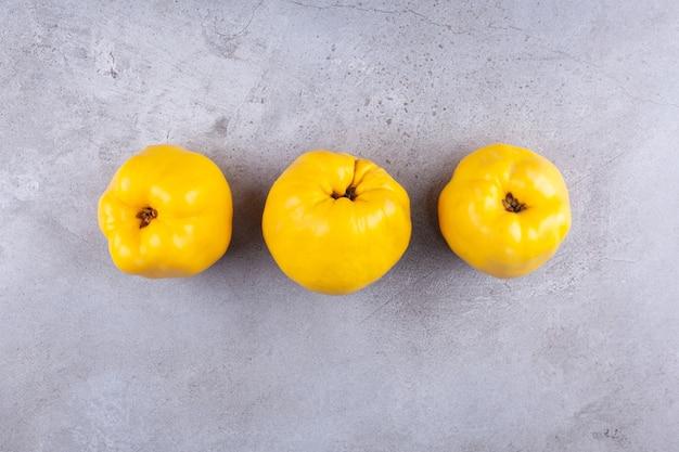 Trois fruits de coing jaune mûr sur fond de pierre.