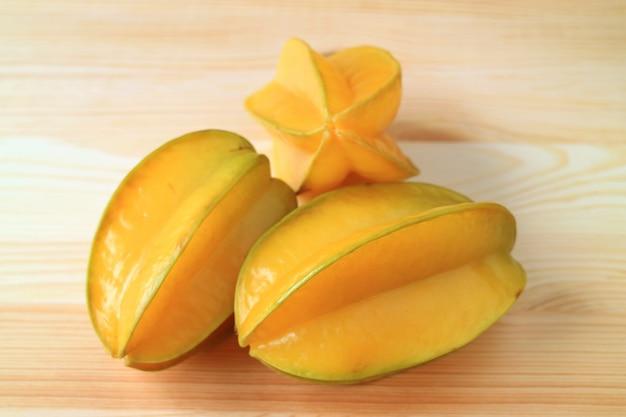 Trois fruits entiers mûrs jaunes vif star fruit sur une table en bois naturel